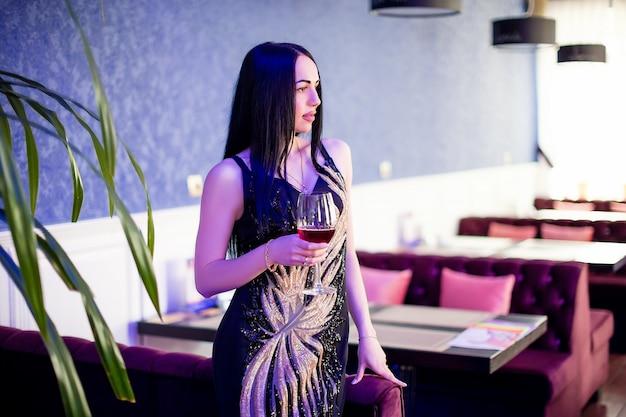 Foto de moda de linda mulher sensual com cabelos cacheados em roupas elegantes no café, bebendo videira Foto Premium