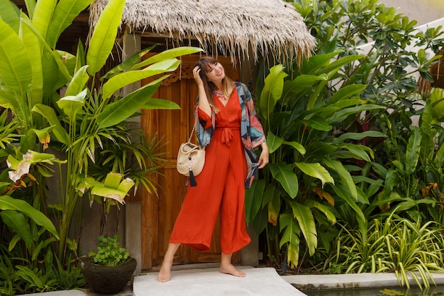 Foto de moda verão ao ar livre de uma linda mulher com roupa de boho, posando em resort tropical de luxo. toda a extensão. plantas tropicais. Foto gratuita