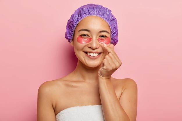 Foto de mulher bonita faz sinal de mão coreano, expressa amor, mostra o gesto do coração com o dedo, usa touca de banho, fica enrolado em uma toalha, aplica adesivos cosméticos nos olhos, sorri feliz. Foto gratuita