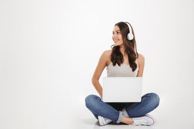 Foto de mulher bonita, ouvindo música ou conversando usando fones de ouvido e laptop enquanto está sentado com as pernas cruzadas no chão, sobre parede branca Foto gratuita