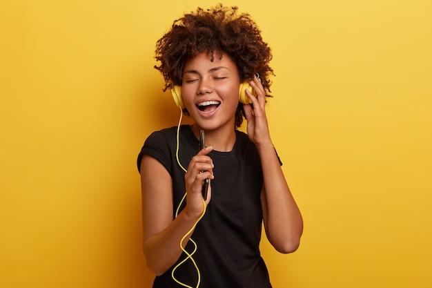 Foto de mulher feliz com a pele escura curtindo o final do dia feliz, ouve música alegre nos fones de ouvido, segura o telefone e fecha os olhos, da cintura para cima Foto gratuita