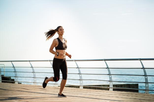Foto de mulher jovem atraente fitness correndo com o mar na parede Foto gratuita