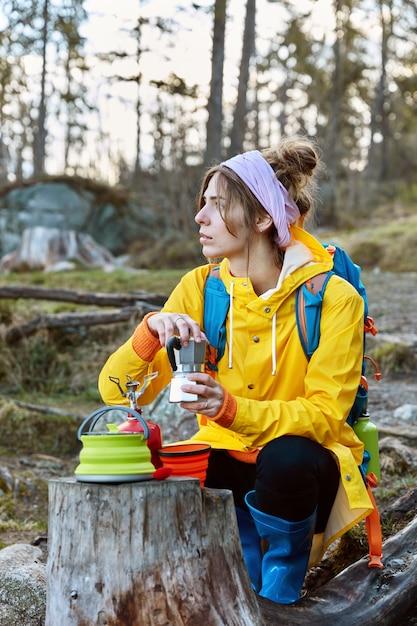 Foto de mulher pensativa tomando café em um local panorâmico, poses perto de um selo com fogão portátil e cafeteira Foto gratuita