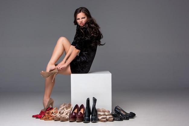 Foto de mulher sentada experimentando sapatos de salto alto Foto gratuita