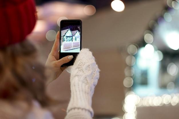 Foto de mulher tomada para smartphone com guirlandas e luzes do feriado na feira festiva de natal ou ano novo. Foto Premium