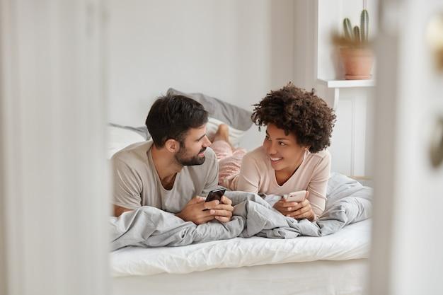 Foto de namorada alegre e namorado pesquisam hotel para ficar durante as férias, navegue pelo aplicativo no smartphone, converse com amigos, desfrute do conforto no quarto. conceito de tecnologias modernas Foto gratuita