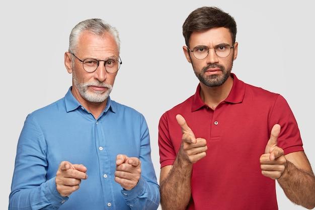 Foto de parceiros masculinos sérios e autoconfiantes de idade diferente apontar diretamente, fazer a escolha, vestir camisa azul formal e camiseta vermelha brilhante, posar juntos contra a parede branca. Foto gratuita