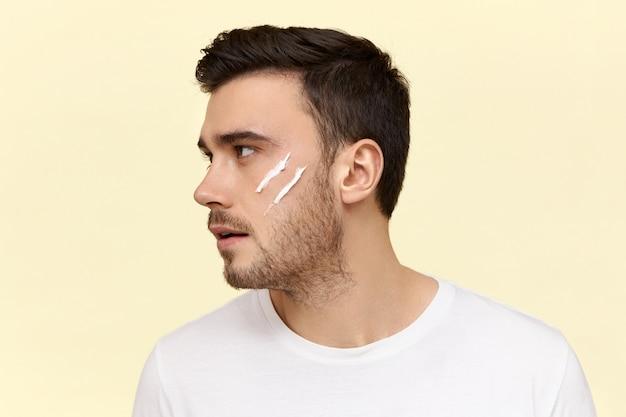 Foto de perfil de jovem europeu confiante e bonito, com penteado elegante e cerdas aplicando hidratante na frente do espelho pela manhã, antes do trabalho. Foto gratuita