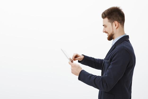 Foto de perfil do empresário elegante, confiante e bem-sucedido, com barba e penteado incrível em um terno elegante usando tablet digital sorrindo encantado, verificando a renda da empresa Foto gratuita