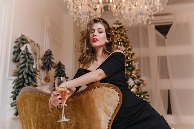 Foto de retrato, mulher gentil e misteriosa com linda manicure e maquiagem brilhante, posando encostada no sofá Foto gratuita