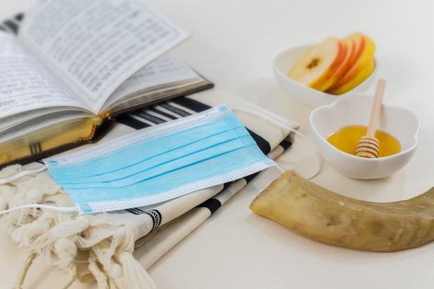 Foto de símbolos do ano novo judaico e uma máscara médica em branco Foto gratuita