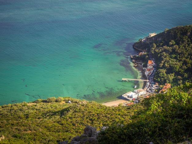 Foto de topo de um pequeno porto próximo a uma floresta no portinho da arrábida Foto gratuita