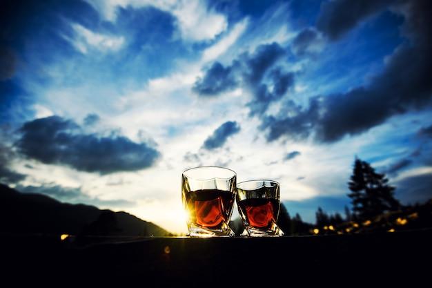 Foto de uísque ao pôr do sol no céu dramático no fundo da paisagem de montanha Foto Premium