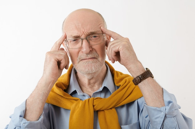 Foto de um aposentado europeu barbudo frustrado pressionando as têmporas com os dedos, apresentando uma expressão facial dolorosa e triste, chorando, sentindo-se estressado por causa de dores de cabeça ou problemas financeiros Foto gratuita