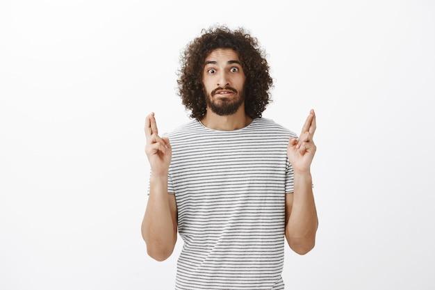 Foto de um cara hispânico barbudo atraente e preocupado com um penteado afro, cruzando os dedos, esperando nervosamente pelos resultados Foto gratuita