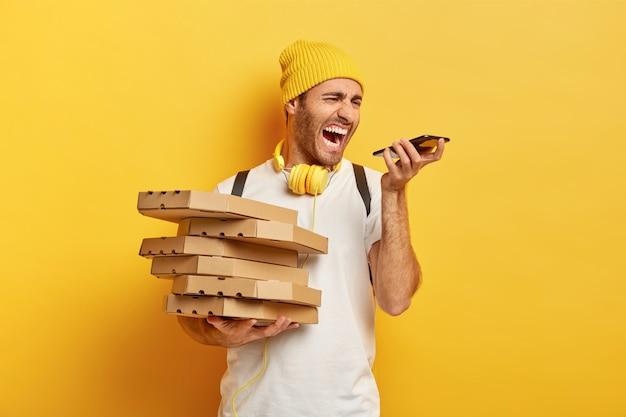 Foto de um entregador de pizza irritado gritando com raiva no smartphone, tendo uma conversa irritante com o cliente, segurando uma pilha de caixas de papelão, usa chapéu e camiseta branca, isolado na parede amarela Foto gratuita