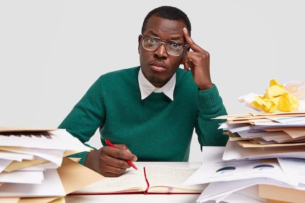 Foto de um estudante de graduação sério e elegante mantém a mão na têmpora, senta-se na mesa, faz anotações no bloco de notas e usa óculos transparentes para correção da visão Foto gratuita