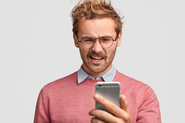 Foto de um estudante descontente segurando um smartphone, curvando os lábios, lendo notícias negativas na internet, vendo fotos horríveis Foto gratuita