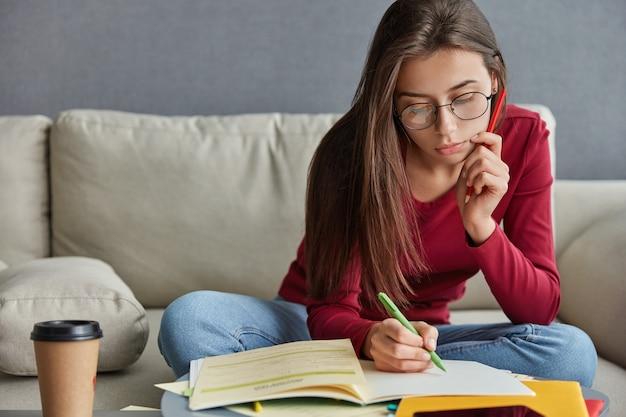 Foto de um estudante sério com uma caneta na mão, escrevendo o curriculum vitae Foto gratuita