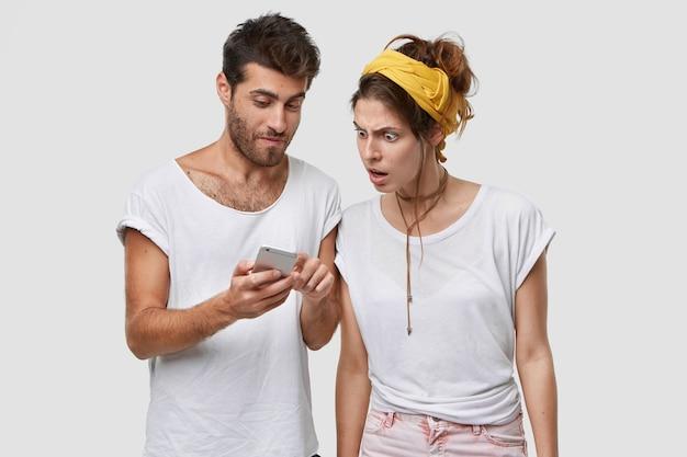 Foto de um homem bonito com a barba por fazer mostra algumas notícias do site para sua mulher europeia, segura o telefone celular, fica em pé sobre uma parede branca, aproveita a internet de alta velocidade em um dispositivo eletrônico Foto gratuita