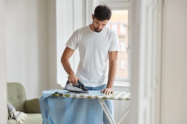 Foto de um homem com a barba por fazer que passa a camisa na tábua de passar roupa se preparando para uma reunião formal em uma conferência de negócios Foto gratuita