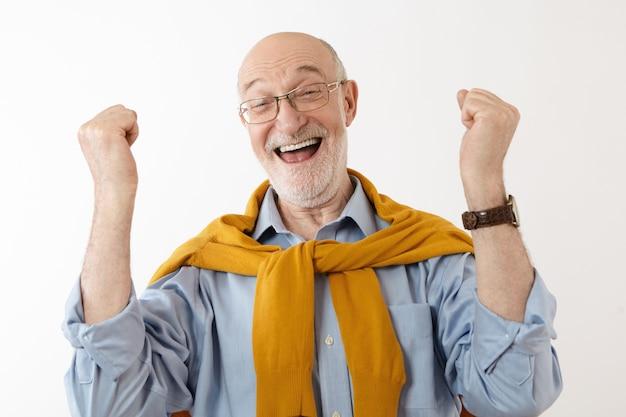Foto de um homem maduro e feliz sentindo-se muito feliz e animado depois de ganhar na loteria, exclamando alegremente, cerrando os punhos. pessoas, sorte, sucesso, empolgação, vitória, vitória e boa fortuna Foto gratuita