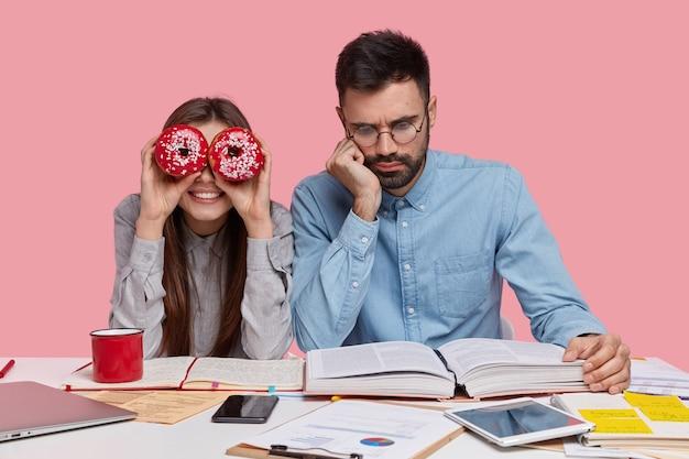 Foto de um homem sério com a barba por fazer usando óculos para uma boa visão, vestido com uma camisa formal, lendo um livro com atenção, uma colega de grupo positiva se divertindo Foto gratuita
