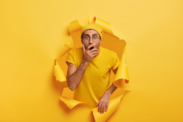 Foto de um homem surpreso e assustado rompe a parede de papel colorido, cobre a boca e tem uma expressão estupefata Foto gratuita