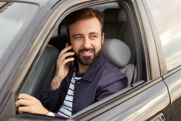 Foto de um jovem atraente e bem sucedido homem barbudo de paletó azul e camiseta listrada, sentado ao volante do carro e aguardando a resposta do telefone. Foto gratuita