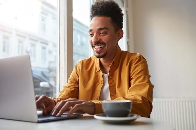 Foto de um jovem atraente garoto afro-americano sorridente, senta-se em um café, trabalha em um laptop e bebe café aromático, conversando com sua namorada e gosta de trabalho freelance. Foto gratuita