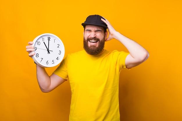 Foto de um jovem barbudo segurando um relógio de parede e fazendo um gesto frustrante. estou atrasado Foto Premium