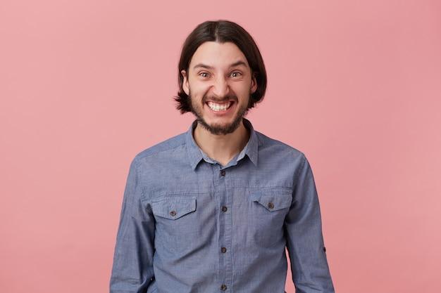 Foto de um jovem barbudo zangado com cabelo escuro comprido penteado de mau humor, parece zangado e descontente isolado sobre um fundo rosa. Foto gratuita