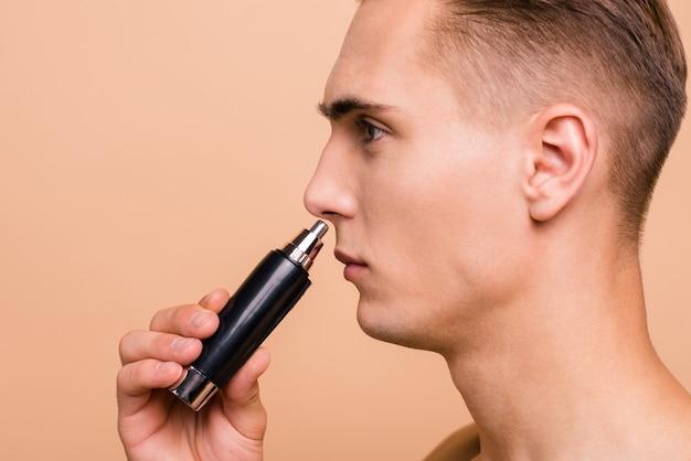Foto de um jovem bonito segurando o aparador para se livrar de pêlos indesejáveis no nariz Foto Premium
