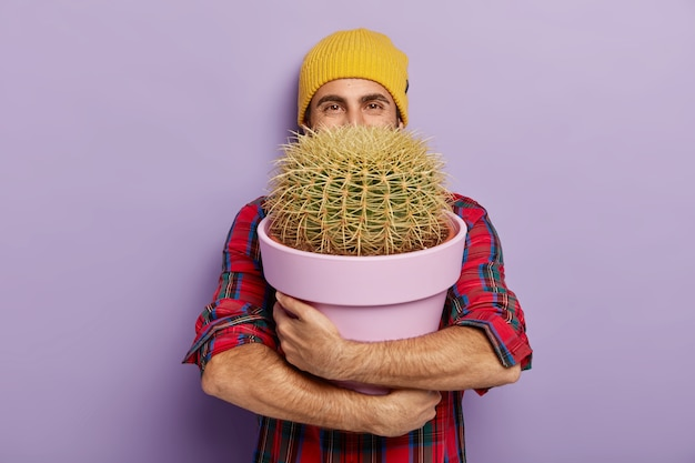 Foto de um jovem cultivador de flores masculino feliz abraça um grande pote com cacto espinhoso, usa um chapéu elegante e uma camisa quadriculada, feliz por receber a planta da casa como presente, isolada na parede roxa. conceito de jardinagem Foto gratuita