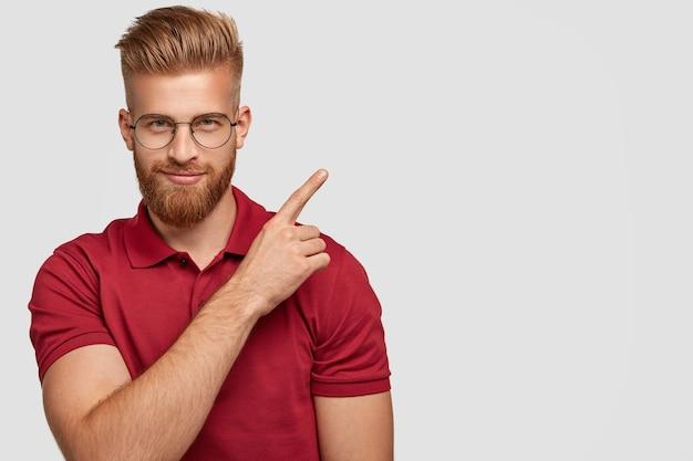 Foto de um jovem ruivo atraente com barba espessa, aponta no canto superior direito, tem uma expressão facial autoconfiante, usa uma camiseta vermelha, isolado sobre uma parede branca com espaço de cópia Foto gratuita