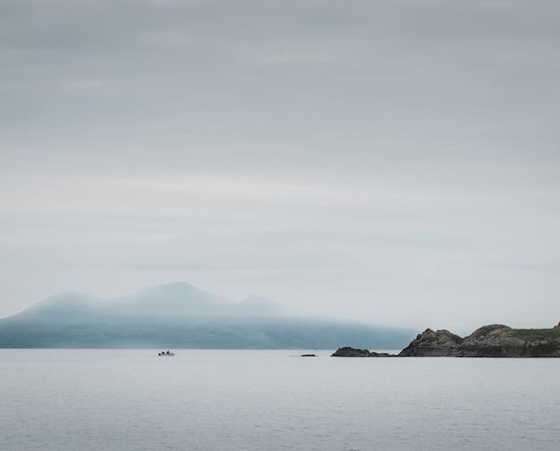 Foto de um lago e penhascos, montanhas enevoadas Foto gratuita