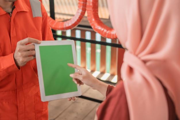 Foto de um mecânico no wearpack usando um tablet digital com um cliente Foto Premium