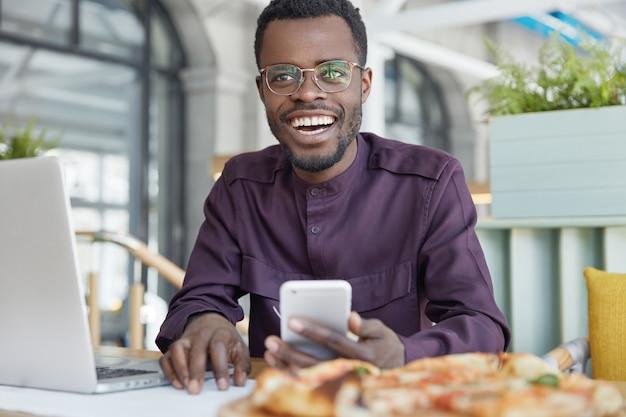 Foto de um próspero gerente de escritório de pele escura usa celular moderno para enviar mensagens, funciona em um laptop portátil Foto gratuita
