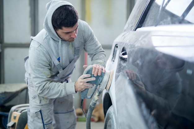 Foto de um reparador profissional preparando o veículo para a nova pintura Foto gratuita