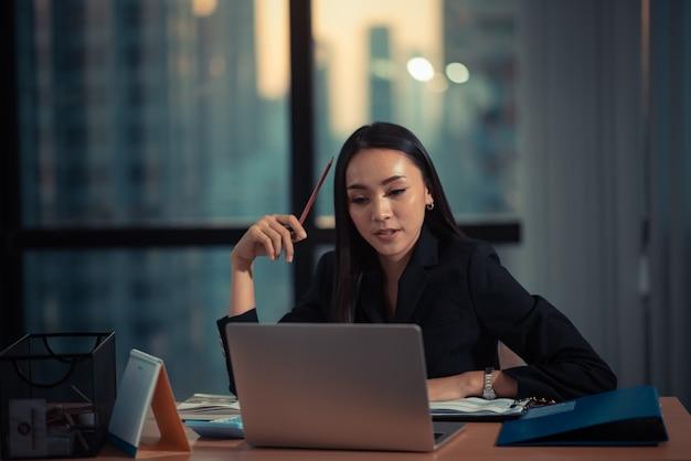 Foto de uma bela jovem empresária usando laptop e fazendo alguns papéis enquanto trabalhava no laptop Foto Premium