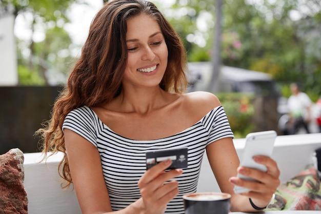 Foto de uma bela turista usando um telefone moderno e um cartão de crédito para reservar a passagem online Foto gratuita