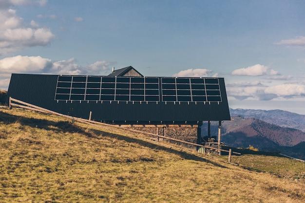 Foto de uma casa na montanha, no telhado de um painel solar, pôr do sol Foto Premium