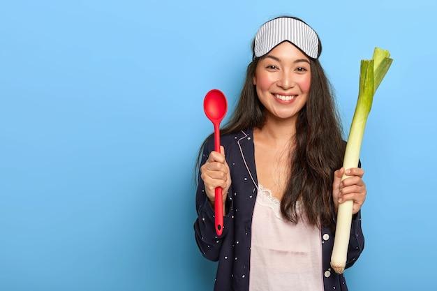 Foto de uma dona de casa feliz indo cozinhar um prato saudável pela manhã, segura alho-poró verde e uma colher vermelha, sorri agradavelmente, usa roupa de dormir Foto gratuita