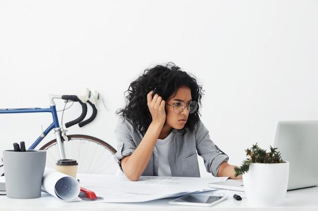 Foto de uma empresária de negócios cansada, de pele escura, usando óculos grandes Foto gratuita