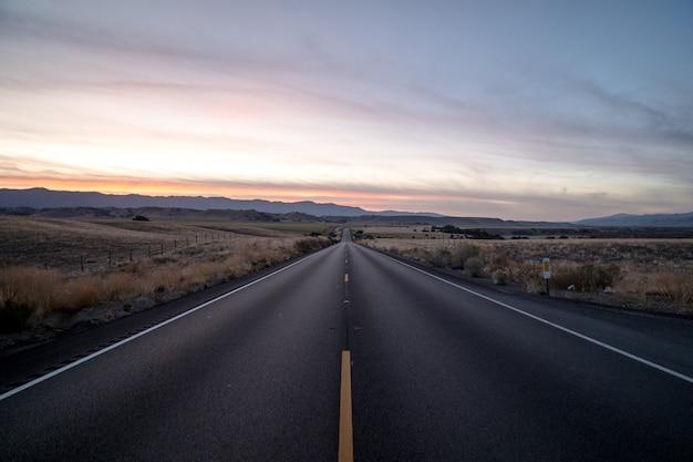 Foto de uma estrada rodeada por campos de grama seca sob um céu durante o pôr do sol Foto gratuita