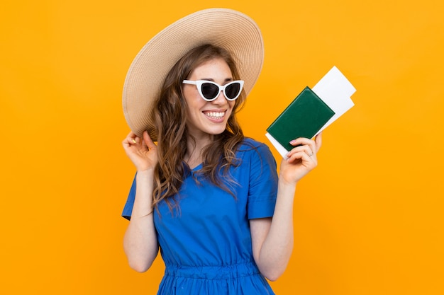 Foto de uma garota de turista com um bilhete e um passaporte nas mãos dela no contexto de uma parede laranja Foto Premium