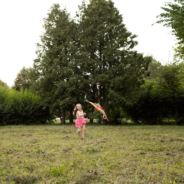Foto de uma garota feliz se divertindo com uma pipa Foto gratuita