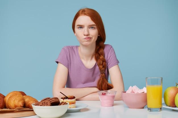 Foto de uma garota ruiva olhando para a câmera com raiva e descontentamento, dúvidas sobre dieta, calorias extras, assando alimentos e frutas frescas Foto gratuita