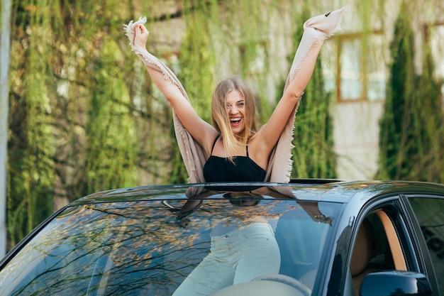 Foto de uma jovem alegre usando óculos escuros e mãos levantadas no teto solar de um carro de luxo Foto gratuita