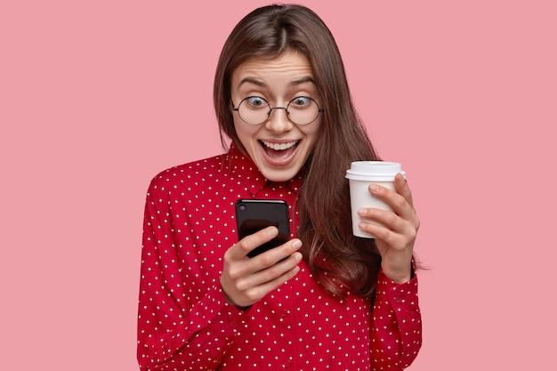 Foto de uma jovem alegre verifica as redes sociais, joga no telefone, acessa aplicativos on-line, bebe café para viagem, vestida com roupas vermelhas Foto gratuita